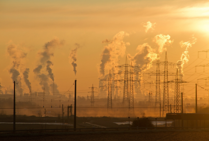 Industrial smoke rises from towers in the distance at dawn.