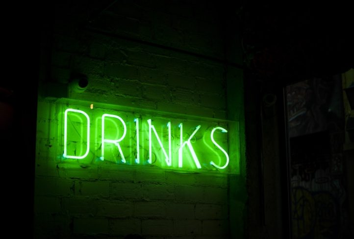 A neon sign announces that drinks are available.