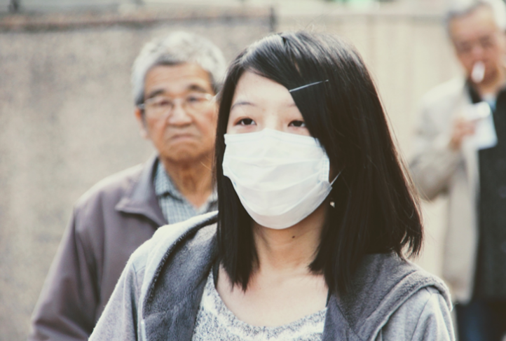 A woman wears a mask to protect against illness.