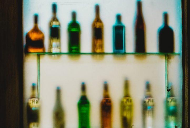 Alcohol bottles sit behind a bar.