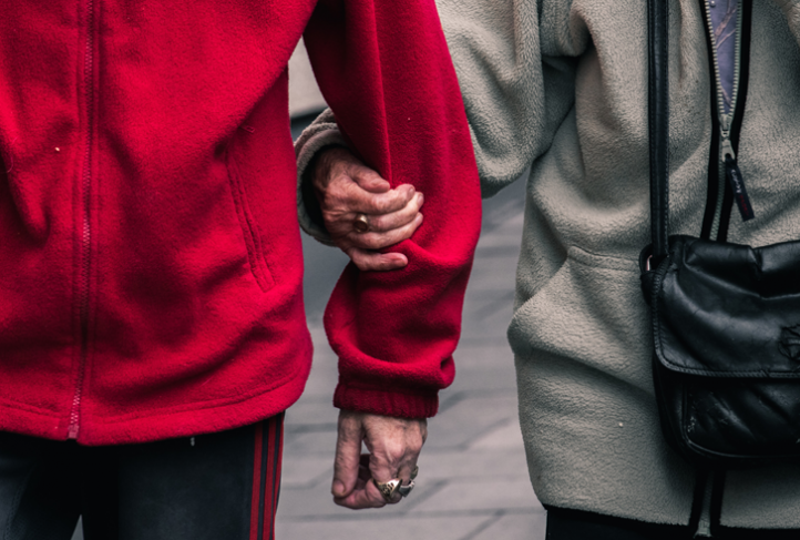A person holds the arm of another person in a red sweater.