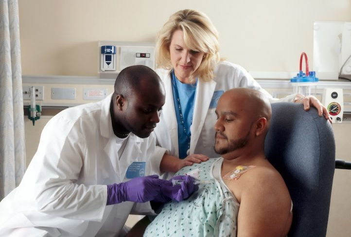 A patient receives Chemotherapy through a port placed in his chest. A nurse looks on.