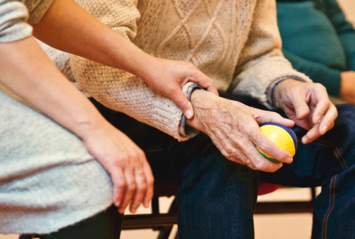 A person gently holds onto the wrist of an elderly person.
