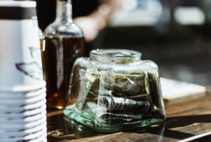 A tip jar sits on a bar.