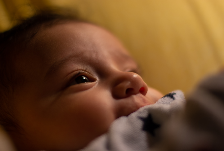 A newborn baby peers upward.