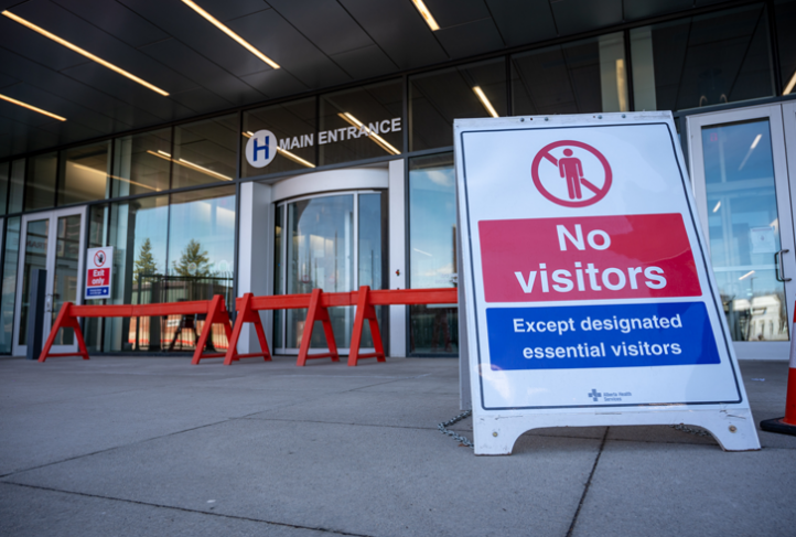 A sign outside a hospital door prohibits visitors from entering unless designated essential
