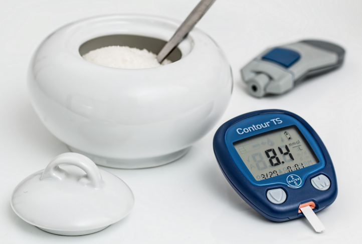 Blood glucose testing supplies sit next to a bowl of sugar.
