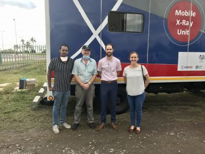 Michael Wilson and colleagues stand in front of a mobile x-ray unit in Durban, South Africa.