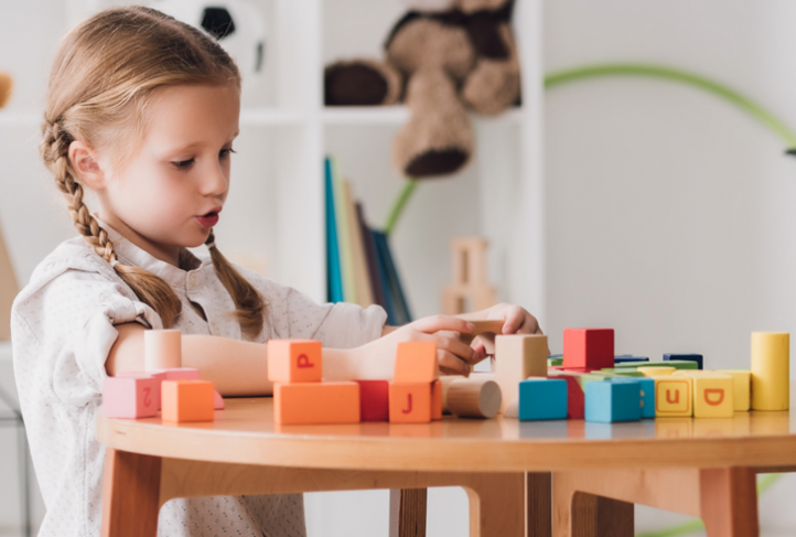 A child plays with colorful blocks at a table. (Photo courtesy of the CDC 2020 Community Report on Autism)