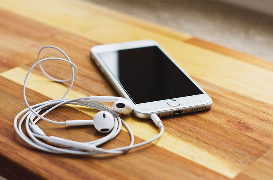 A phone with headphones plugged in sits on the table.