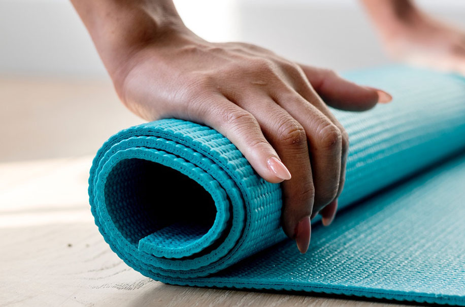 A woman rolls up a yoga mat.