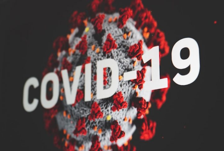 "The word ""COVID-19"" overlays a close-up view of the novel coronavirus."