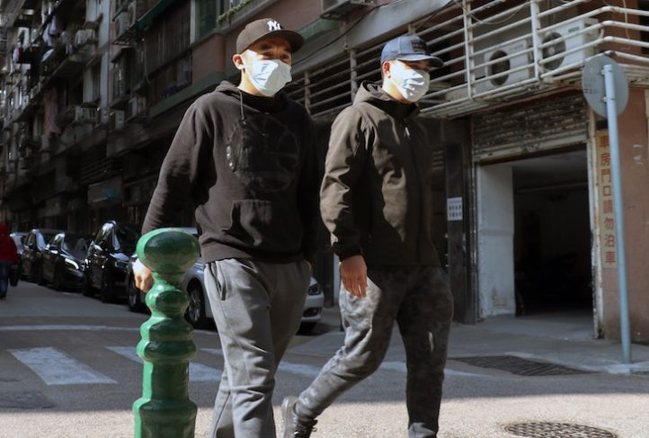 Men wear protective masks in the street.