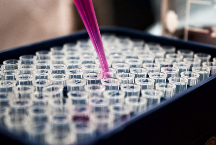 A pipette holds purple liquid.