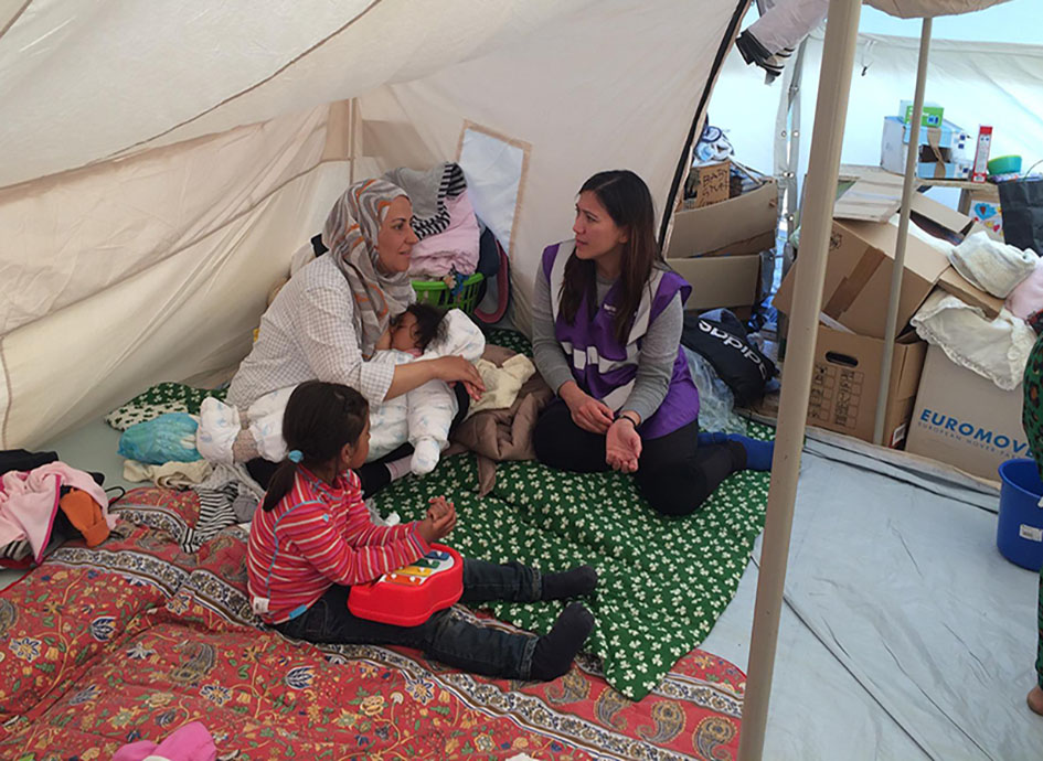Dr. Palmquist sitting with a breastfeeding parent and small child on the floor of a white tent.