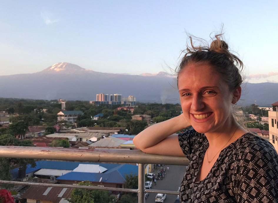 Lizzy Knippler standing outside with Mt. Kilimanjaro in the background.