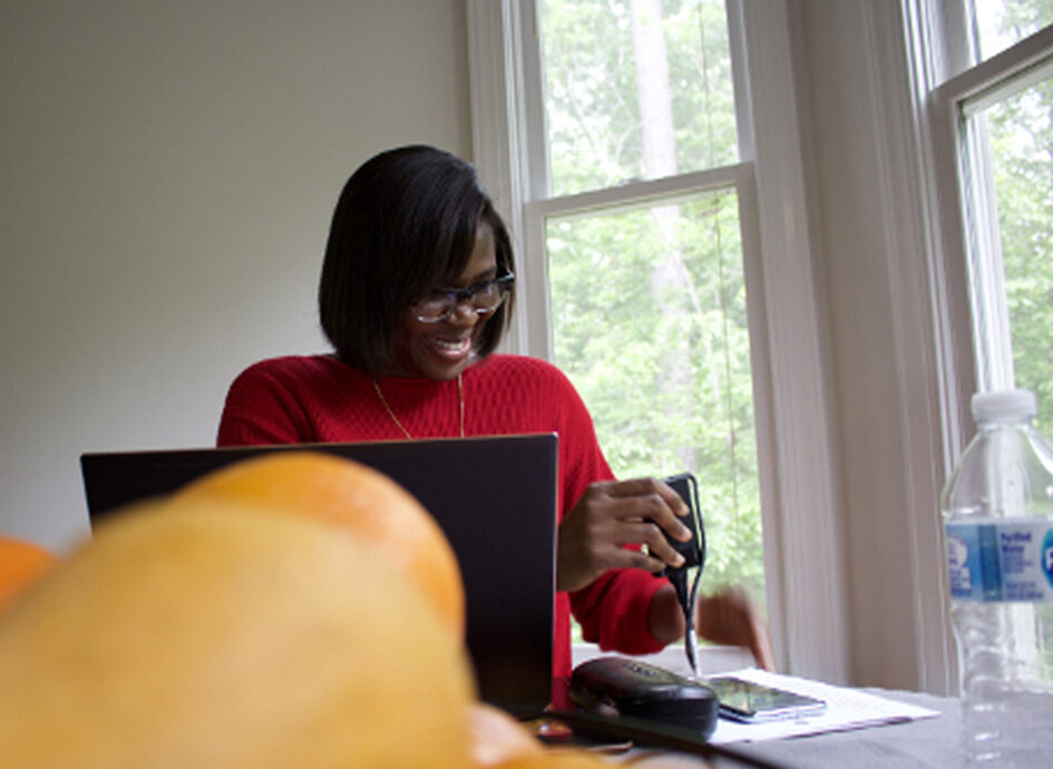 Doreen Ankamah sitting at a desk with a laptop, water bottle, and a bowl of oranges.