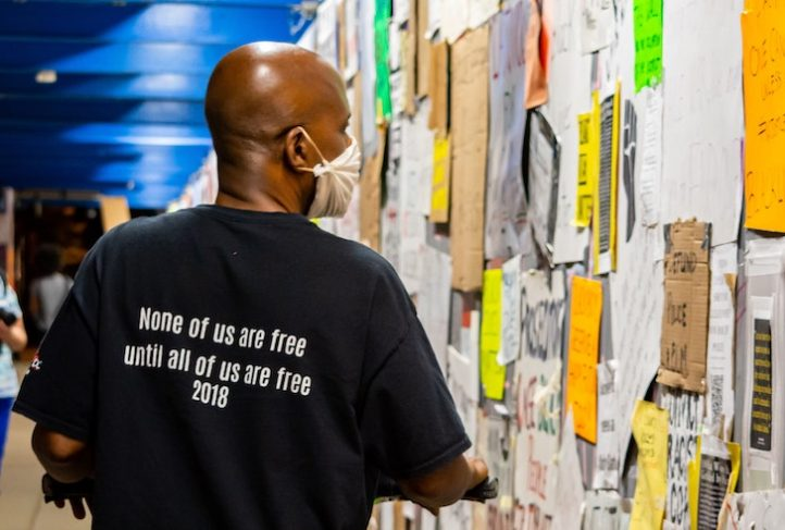 "A man wears a shirt that reads, ""None of us are free until all of us are free."""