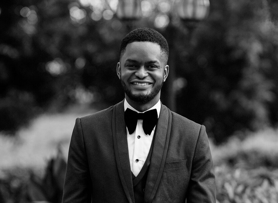 Olu Adeniran standing in front of a wooded scene