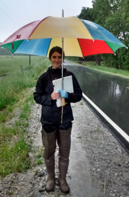 Dr. Christenson-Diver waits out the rain during field work.