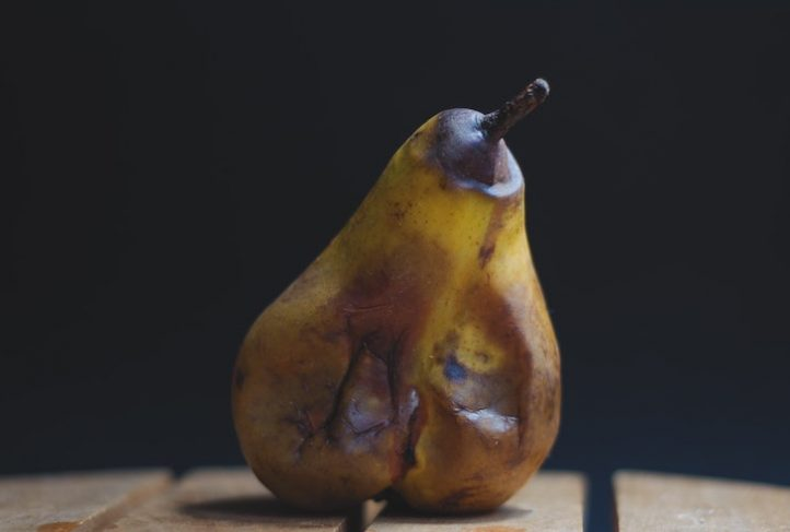 A rotten pear rests on a table.