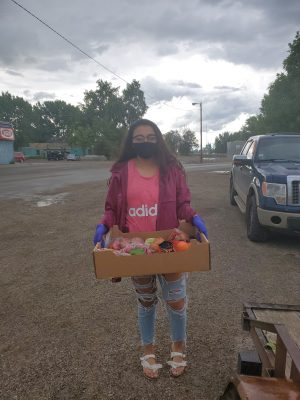 A woman carries food provided with help from the Native American Community Response Fund.