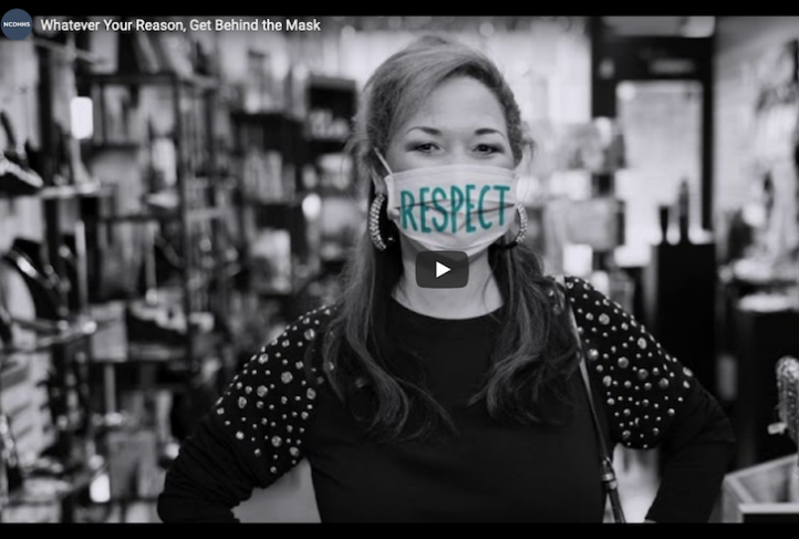 "This screenshot displays a paused video that is part of the NCDHHS ""Whatever your reason, get behind the mask"" campaign."