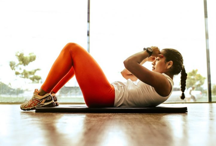 A person does sit-ups on a yoga mat.
