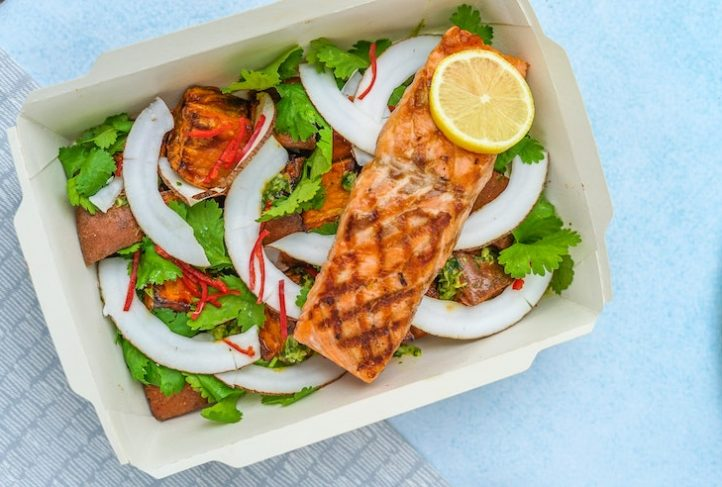 A takeout container holds a salmon meal.