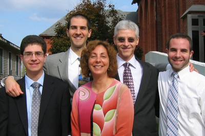 Dr. Michael Aitken (in sunglasses) smiles with his wife and three sons.