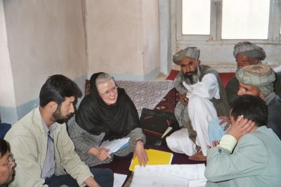Sallie Craig Huber discusses community health mapping with community elders in a village in Afghanistan.