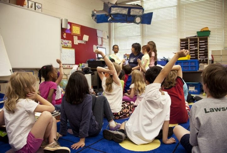 A child care teacher leads story time at a daycare center.