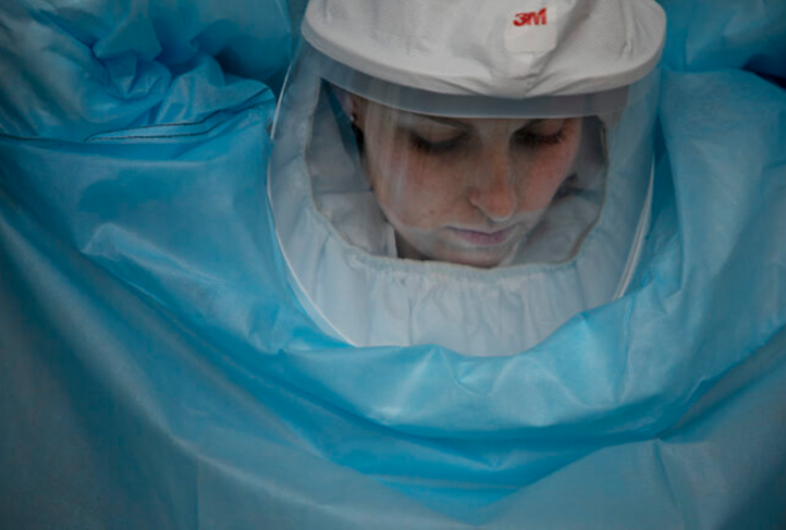 A researcher at the BSL-3 lab dons personal protective equipment.