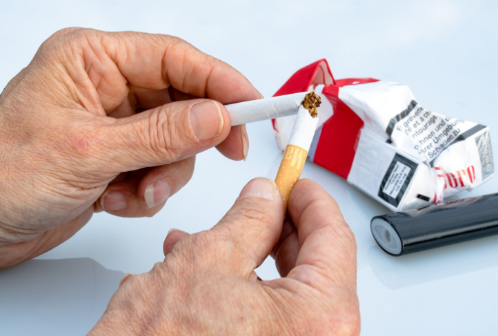 Hands break a cigarette in half from a crumpled cigarette pack.