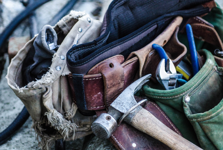 A belt full of construction tools and gloves rests on the ground.