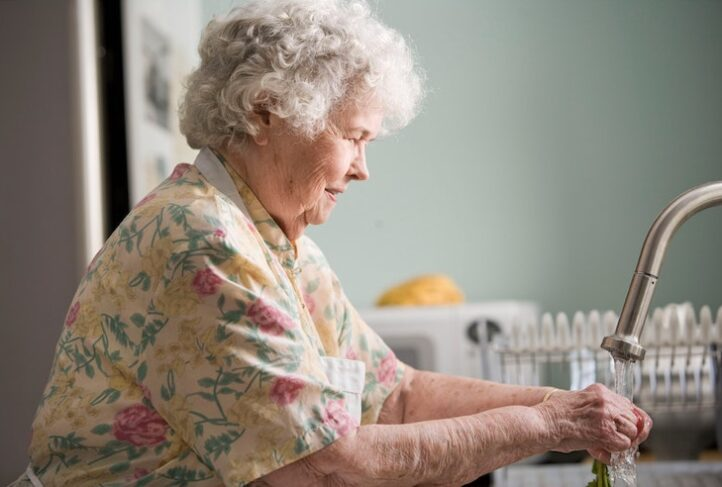 An elderly woman washes her hands.