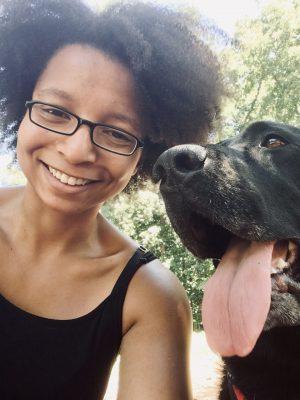 Mya smiles with her dog, Malcolm.