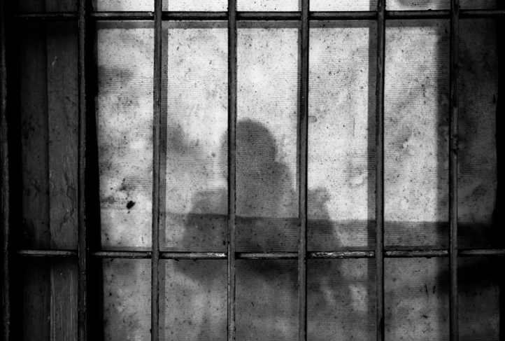 A person's shadow is cast on a barred wall.
