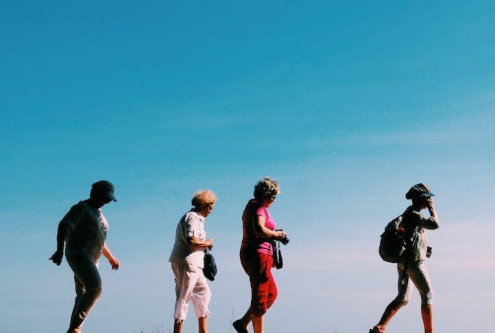 Women walk in silhouette against a blue sky.