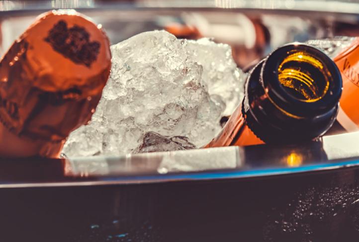 Bottles sit in a bucket of ice.