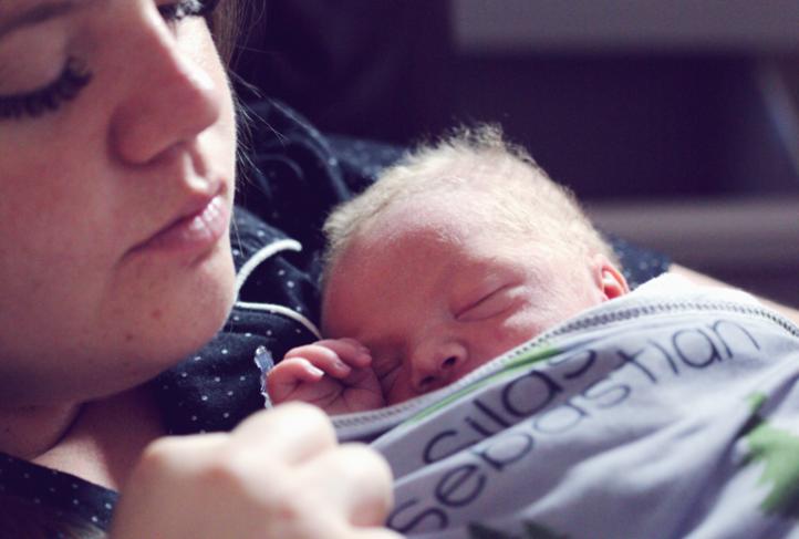 A woman holds her newborn close.