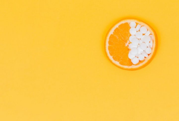Dietary supplement pills fill the rind of an orange.