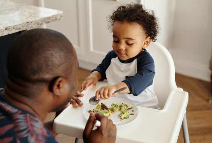 A father feeds a child in a high chair.
