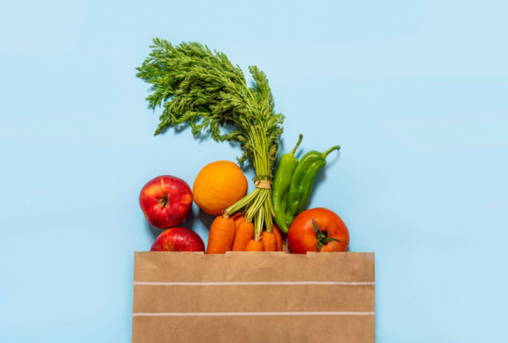 A bag of groceries contains fresh fruit and vegetables.