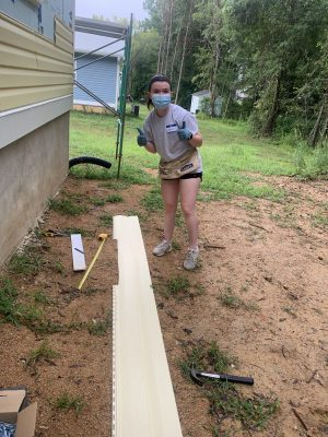 Jaycee Reilly gives a thumbs up in the midst of construction work with Habitat for Humanity.